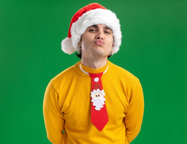 Happy young man in yellow turtleneck and santa hat with funny tie keeping lips like going to kiss standing over green background