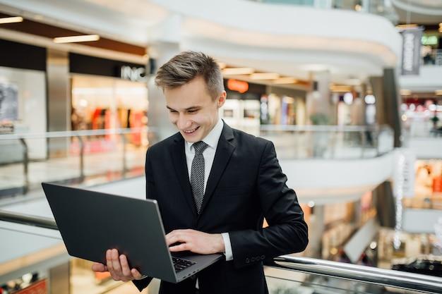 ラップトップでインターネット上でチャットしている幸せな若いマネージャー、黒いスーツを着て、ビジネスセンター、屋内、前向きな顔の感情