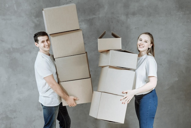 Happy young married couple man and woman with boxes for moving in new home