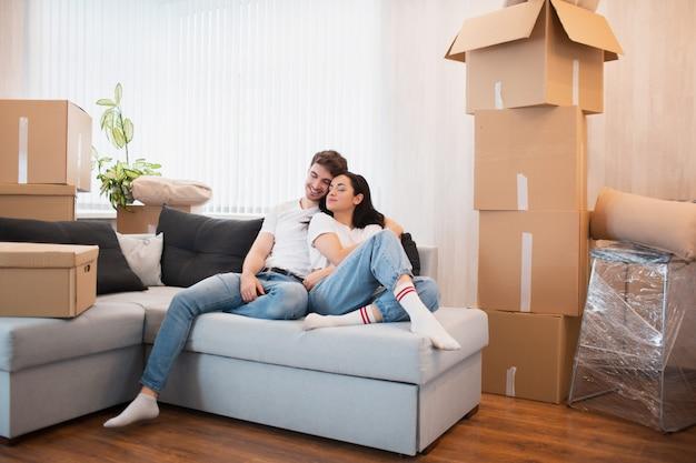 Счастливая молодая семейная пара переезжает в новую квартиру. они сидят на диване и смотрят на свой новый дом.