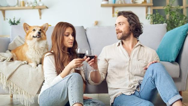행복한 젊은 부부는 소파 근처 바닥에 앉아 와인으로 안경을 부딪치며 새 집 구입, 성공적인 모기지 투자를 축하합니다. 부부 사이에 앉아있는 귀여운 강아지.