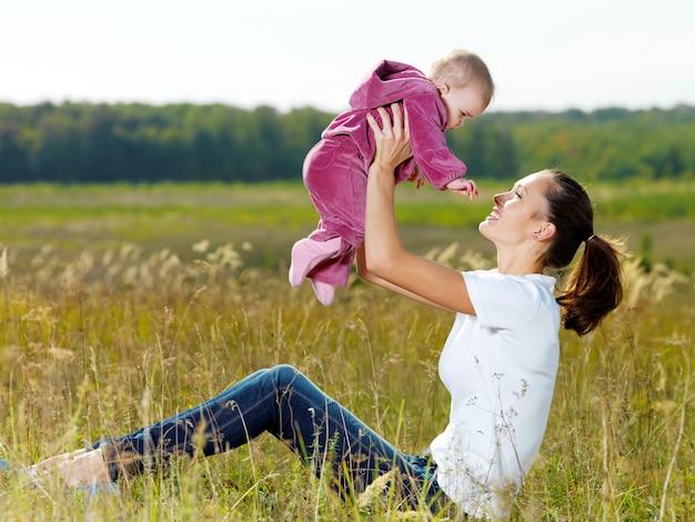 Счастливая молодая мама играет с улыбающимся ребенком