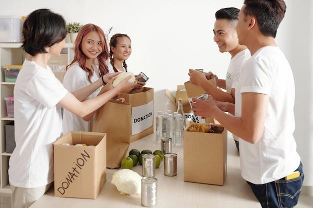 Счастливые молодые мужчины и женщины складывают консервы, овощи и другие продукты в бумажные пакеты для нуждающихся