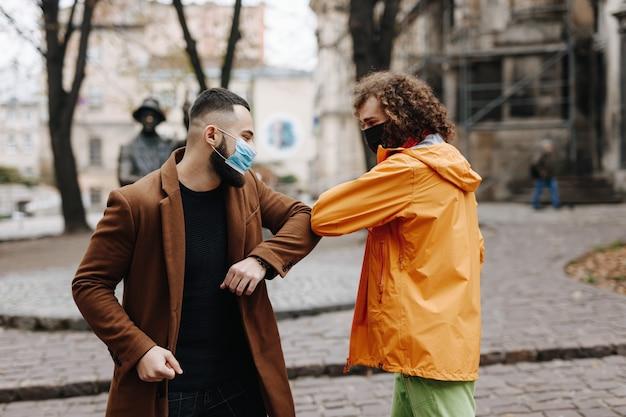 通りで会う間、肘で挨拶する医療マスクの幸せな若い男性。屋外での検疫措置を受けた2人の多民族の人々。