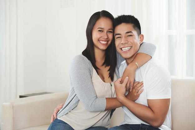 Happy young mixed race couple hugging and smiling at home