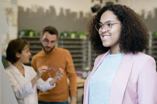 Счастливая молодая женщина смешанной расы в очках смотрит в зеркало, пока продавец помогает клиенту-мужчине с выбором