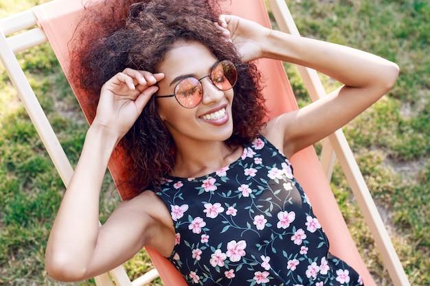 Giovane donna rave mista felice con i capelli ricci stupefacenti che si rilassano sulle chaise longue su prato inglese verde in parco