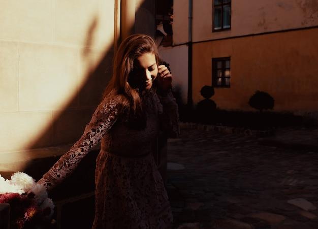 花の花束を保持している幸せな若いモデル。彼女の顔に影を付けて通りでポーズをとる女性