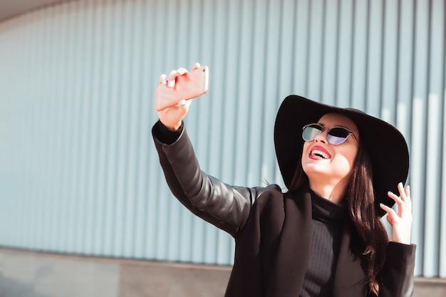 スマートフォンで自分撮りをしている幸せな若いモデル。女性は帽子とサングラスを着用します