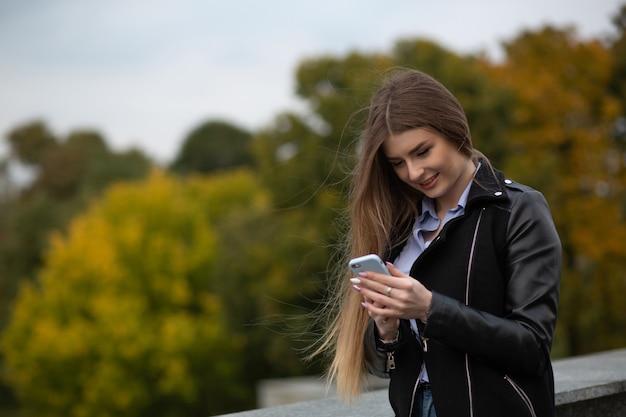 スマートフォンを使用してメッセージを入力する幸せな若いモデル。テキスト用のスペース