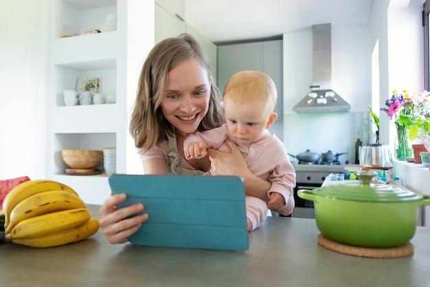 幸せな若いお母さんと赤ちゃんが一緒にキッチンで料理をしながらタブレットでオンラインビデオ料理コースを見てください。育児や家庭料理のコンセプト