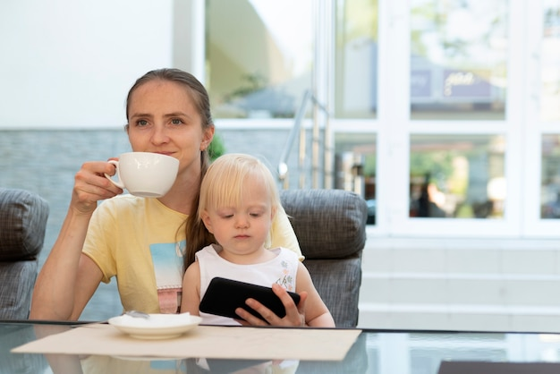 幸せな若いお母さんはコーヒーを飲み、子供を抱きしめます。お母さんがリラックスしている間、電話で漫画を見ている子供。