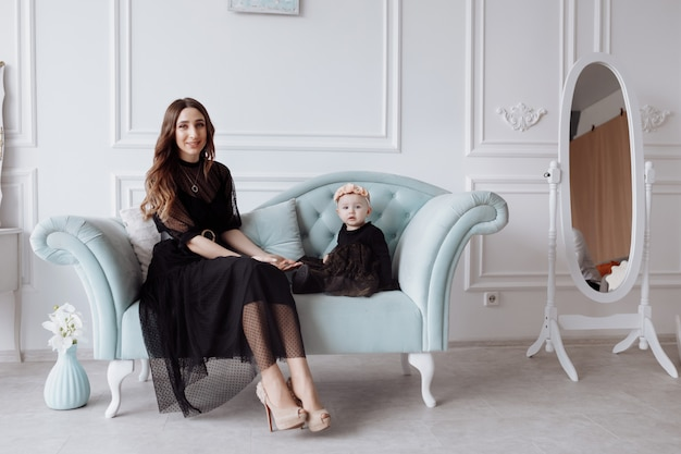 Happy young mom on stylish couch relax with little daughter in black dresses and posing, smiling mother and girl child have fun at studio. family look
