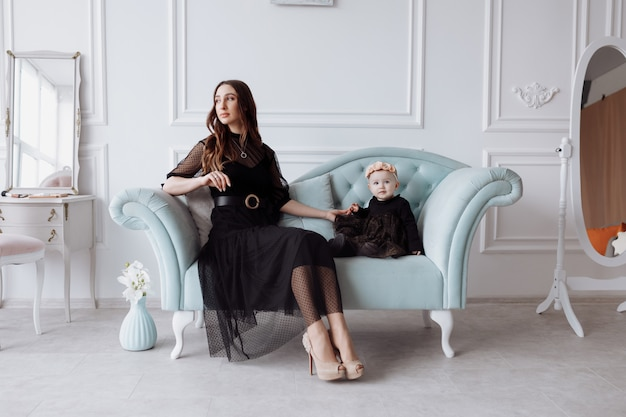 Happy young mom on stylish couch relax with little daughter in black dresses and posing, smiling mother and woman child have fun. family look