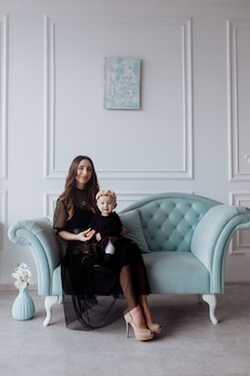 Happy young mom on stylish couch relax with little daughter in black dresses and posing, smiling mother and woman child have fun at studio. family look