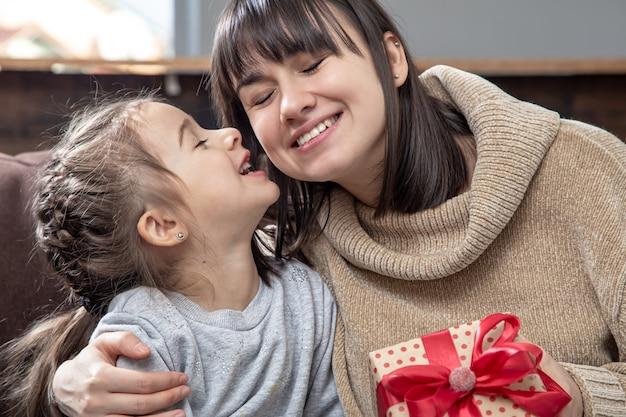 Счастливая молодая мама с милой дочерью. концепция поздравления с праздником, семейных отношений и качественного времени вместе.
