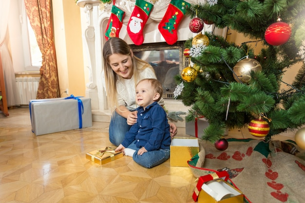 Happy young mother and 1 year old baby boy on floor under christmas tree at living room