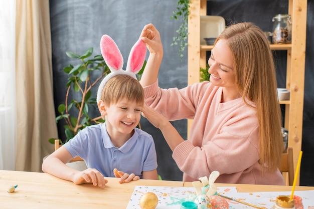 彼らがイースターパーティーのために服を着ている間、幸せな若い母親は息子の頭にウサギの耳のヘッドバンドを調整します