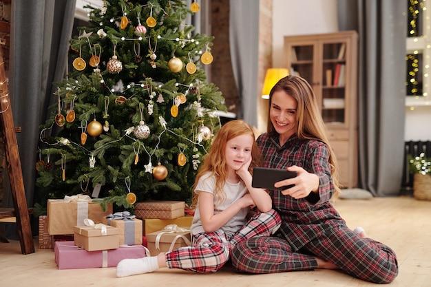 幸せな若い母親とパジャマを着た愛らしい小さな娘がリビングルームの床に座って飾られたクリスマスツリーで自分撮りを作る