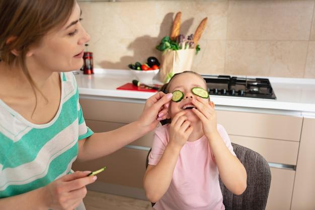 Счастливая молодая мать и дочь с удовольствием на кухне, концепция семьи счастливой матери-одиночки