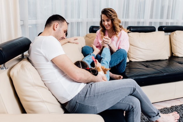 행복 한 젊은 어머니와 아버지는 소파에 앉아 작은 딸과 함께