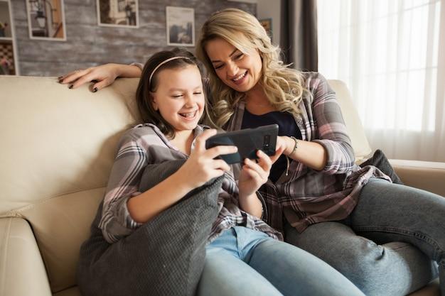 幸せな若い母と彼女の子供はソファに座ってスマートフォンを使用しながら笑っています。