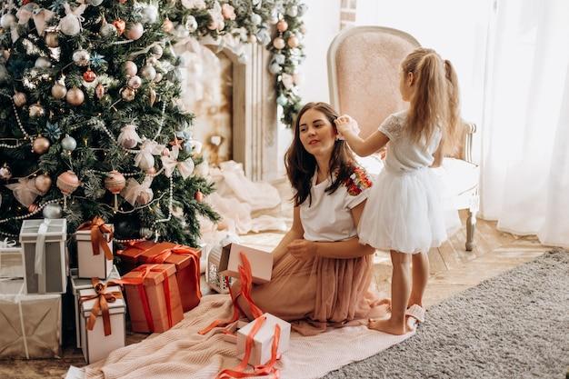 Счастливая молодая мама и ее маленькая дочка в красивом платье сидят у новогодней елки и открывают новогодние подарки в светлой уютной комнате.