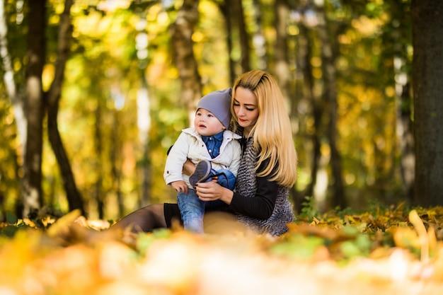 幸せな若い母親と幼い息子が秋の公園で時間を過ごします。