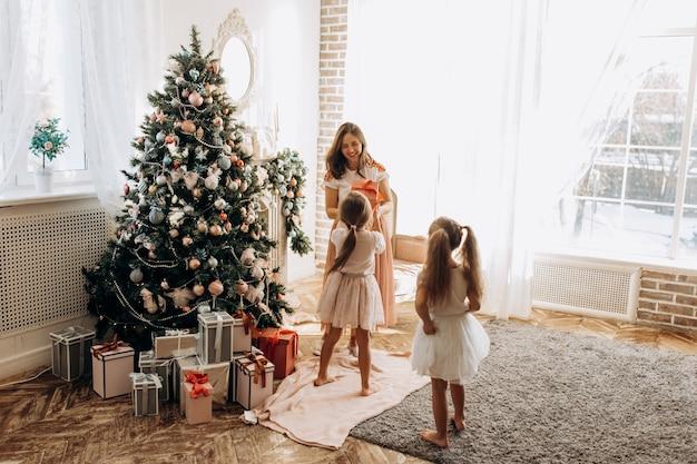Счастливая молодая мама и две ее очаровательные дочки в красивых платьях стоят у новогодней елки и принимают подарки в светлой уютной комнате.