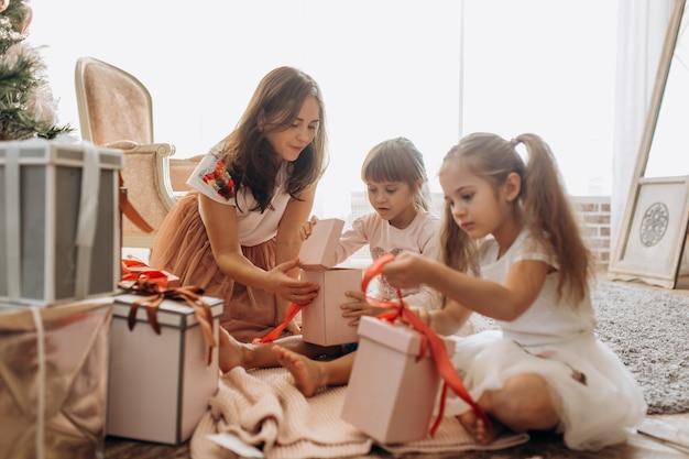 Счастливая молодая мама и две ее очаровательные дочери в красивых платьях сидят на ковре и открывают новогодние подарки в светлой уютной комнате.
