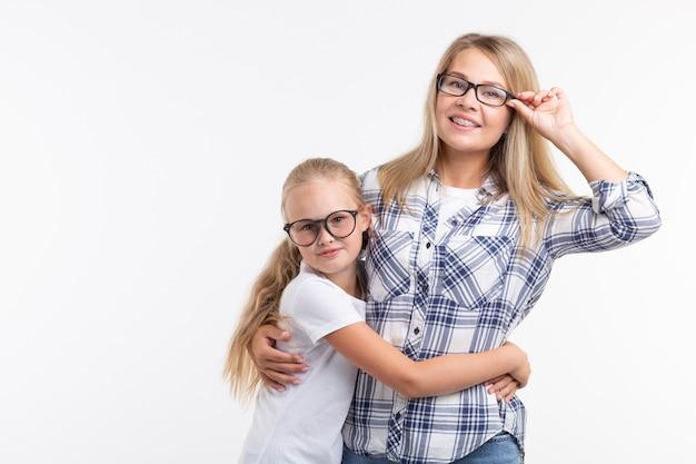 幸せな若い母親とファッションメガネで笑っている子供は白い背景で楽しんでいます