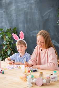 テーブルに座って親戚のためのイースターカードを準備しているウサギのヘッドバンドで幸せな若い母と息子