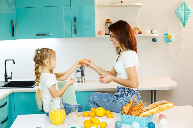 Happy young mother baking croissant for her daughter in the kitchen at home. happy family relationships