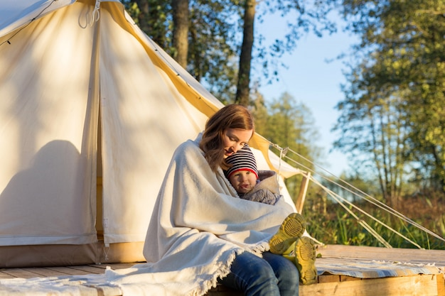 Happy young mother embracing her toddler girl with a blanket while sitting near canvas tent