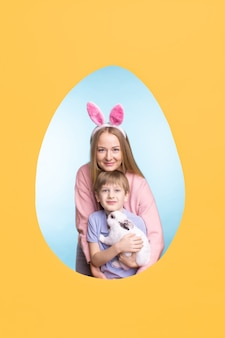 Happy young mother embracing son with cute bunny while posing in easter egg frame