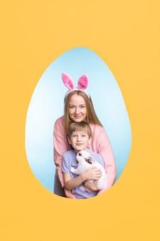 イースターエッグフレームでポーズをとっている間、かわいいウサギと息子を抱きしめる幸せな若い母親