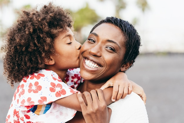 Happy young mother having fun with her child in summer day - daughter kissing her mum outdoor