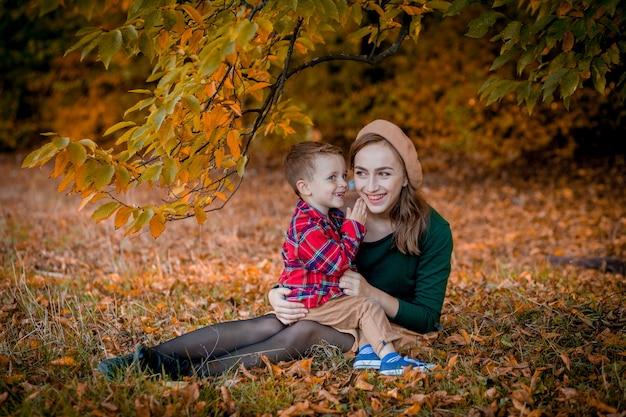 秋の日に彼女の小さな男の子と楽しんで幸せな若い母親
