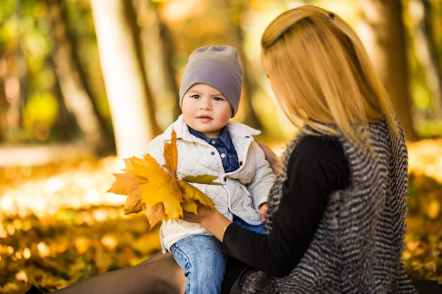 Happy young mother and her little son spending time in the autumn park.
