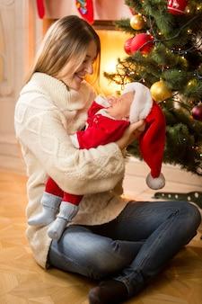 산타 의상에서 아기 아들을 들고 행복 한 젊은 어머니