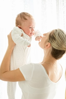 窓際に彼女の生後3ヶ月の赤ちゃんを抱いて幸せな若い母親