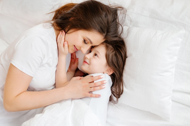 Happy young mother hugs her little daughter in bed