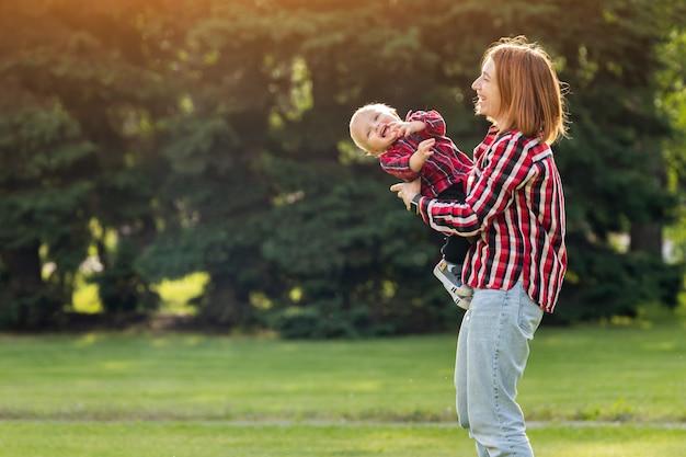 幸せな若い母親は緑の芝生の公園で彼女の赤ちゃんと遊んでいます。