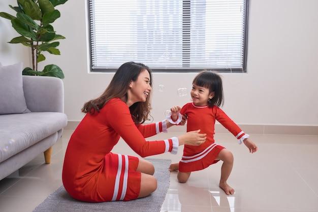 아침에 어린 딸과 함께 웃고 있는 행복한 젊은 어머니. 함께 재미. 집에서 즐거운 가족 시간.
