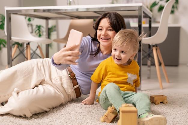 카펫에 누워 셀카를 위해 작은 아들과 함께 포즈를 취하는 동안 스마트 폰을 사용하는 행복 한 젊은 어머니