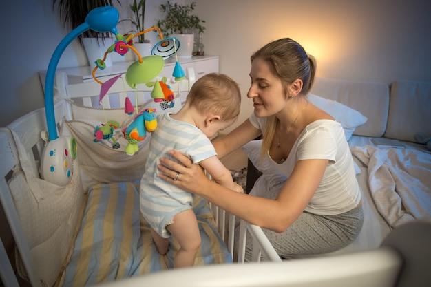 잠들기 전에 아기 침대에서 아기를 바라보는 행복한 젊은 어머니