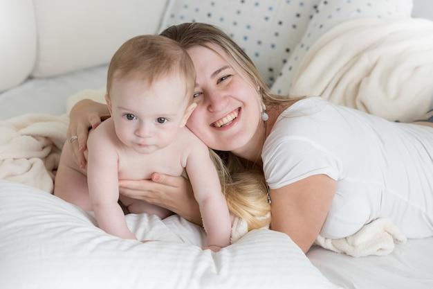 彼女の9ヶ月の赤ちゃんと一緒に大きな枕の上に横たわっている幸せな若い母親