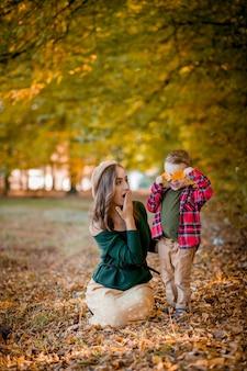 Счастливая молодая мать играет и веселится со своим маленьким сыном в солнечный теплый осенний день
