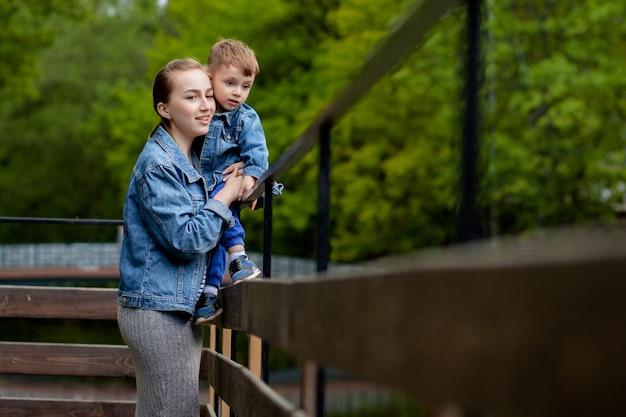 公園で暖かい春や夏の日に彼女の小さな赤ちゃんの息子を遊んで楽しんで幸せな若い母。幸せな家族の概念、母の日