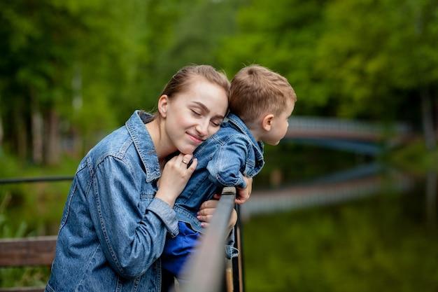幸せな若い母親は、公園で暖かい春や夏の日に彼女の小さな赤ちゃんの息子と遊んで楽しんでいます。幸せな家族の概念、母の日。